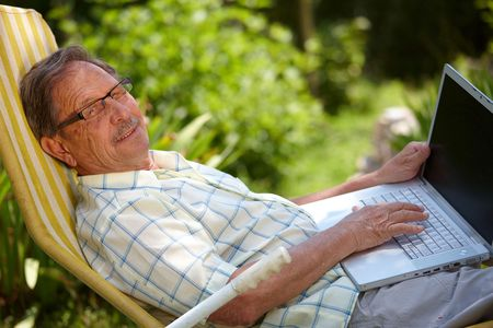 Happy senior man is his elderly 70s sitting outdoor in garden at home and using laptop computer to browse internet, smiling. Stock Photo - 3823736