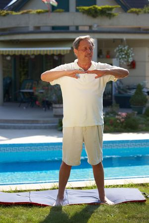 Healthy looking active senior man doing workout exercise. photo