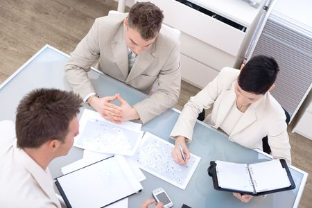 High-angle view of businesspeople having a meeting at office, sitting around the desk and talking. photo