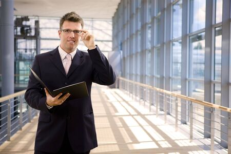 Happy single businessman holding folder, smiling at office lobby. photo