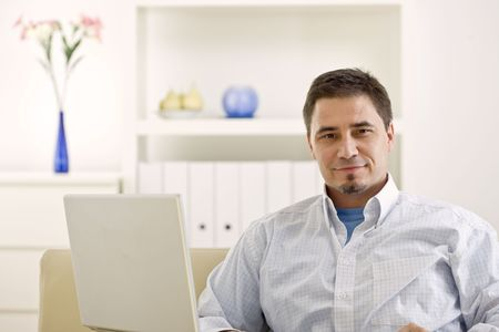 Happy casual man teleworking using laptop computer at home. Stock Photo - 3823804