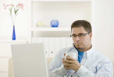 Casual man using laptop computer at home drinking coffee. photo
