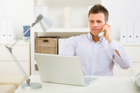 outworking: Business man working on laptop computer at home and calling on phone.