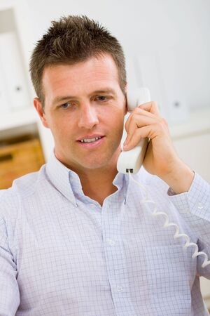 outworking: Business man working at home, calling on phone.