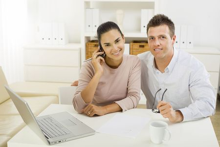 Couple working on laptop computer at home office, happy, smiling. Stock Photo - 3823801