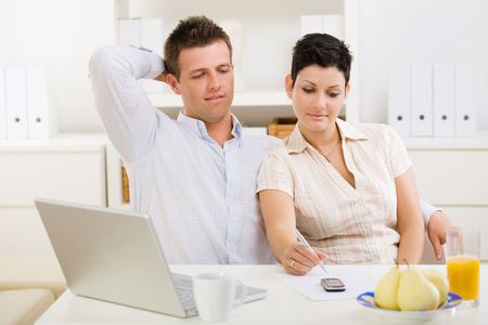 outworking: Couple working on laptop computer at home office. Stock Photo