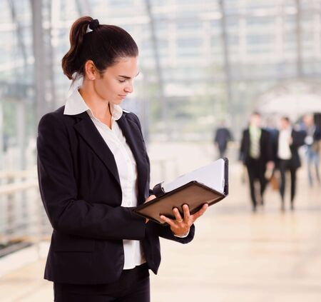 Attractive businesswoman looking at day planner in office lobby. photo