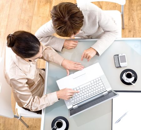 High angle view of businesswomen working together on laptop computer at office. photo