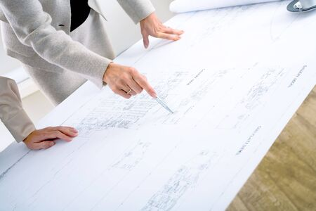 architect office: Close-up of hands of female architects working on blueprint. Stock Photo