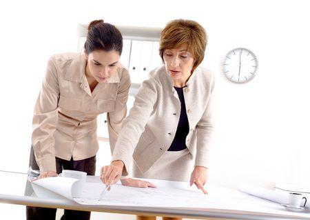 Female architects designing on blueprint at office. photo