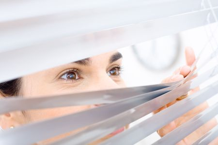 Woman peeping though window blinds, smiling. photo