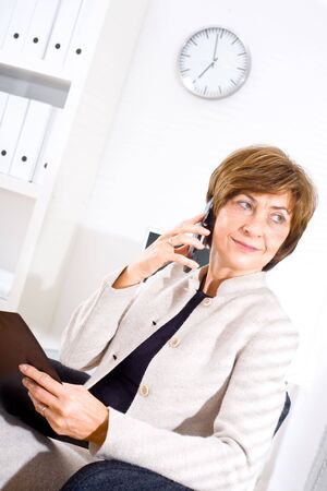 Mature businesswoman talking on cellphone from office. photo