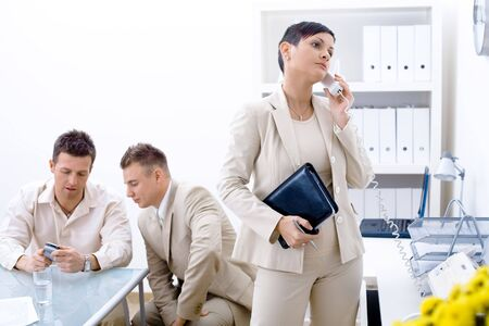 Businessteam of three working at office, businesswoman standing in foreground, calling on phone. photo