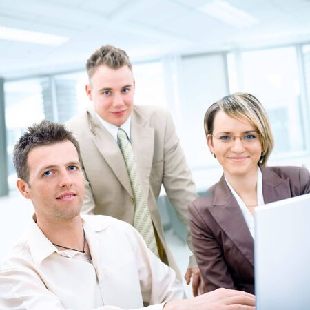 Three business colleagues working together on laptop computer in office, looking at camera, smiling. Stock Photo - 3850829