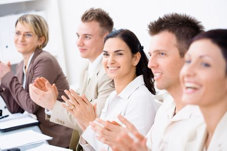 Five business people sitting in a row, smiling and clapping on business training. Selective focus placed on businesswoman in middle. Stock Photo