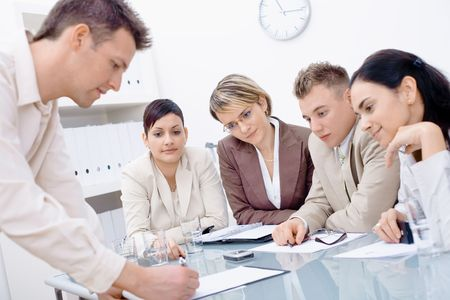 businessmeeting: Businessman leaning on desk, explaining to four colleagues sitting.