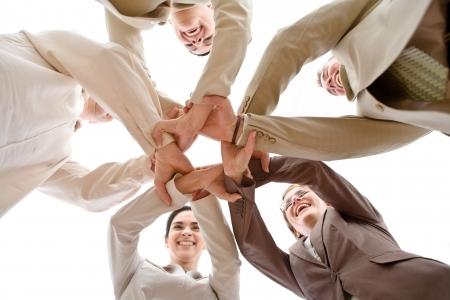 manos unidas: Peque�o grupo de gente de negocios que une manos, el bajo �ngulo de vista. Foto de archivo