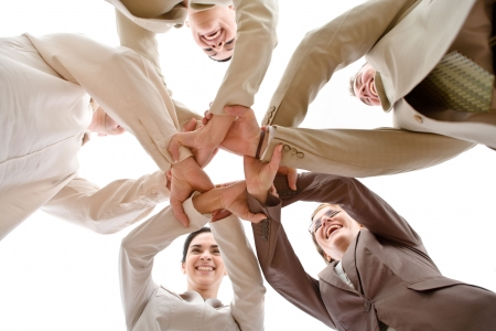 join the team: Small group of business people joining hands, low angle view.