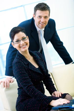 Young and happy businesspeople at office, smiling. Businesswoman sitting on couch while businessman standing and leaning. photo
