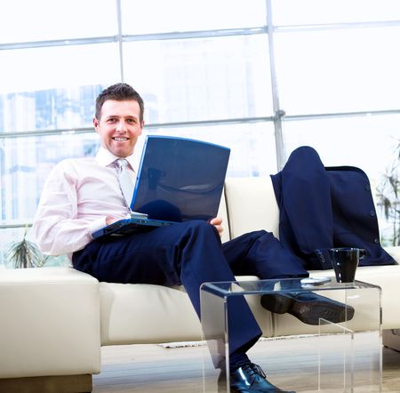 Happy businessman sitting on couch at office, working on laptop computer and smiling. photo