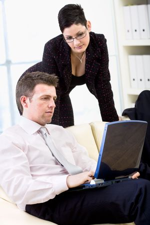 Businessman and businesswoman working together on laptop computer at office. photo