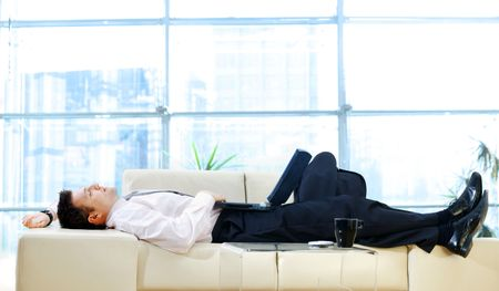 resting: Businessman taking break at office, lying on back and thinking while resting on sofa and holding laptop computer.