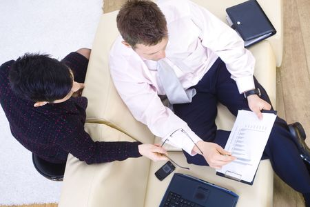 High-angle view business people sitting on couch at office, looking at and analyzing diagram. photo