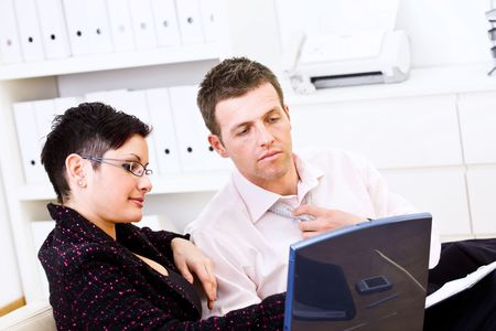 Business partners teamworking at office, sitting on sofa looking at laptop screen. Stock Photo - 3850859