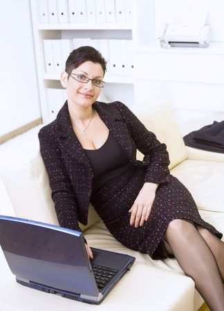 Happy businesswoman sitting on sofa at office and working on laptop computer, smiling. photo