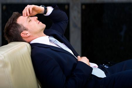 tired eyes: Mid-adult businessman lying on sofa at office, looking tired, eyes closed. Dark background.