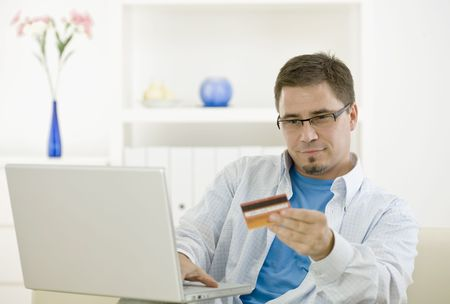 Casual man at home using laptop computer purchasing by credit card.