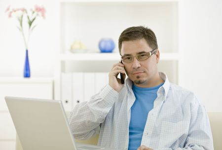 outworking: Casual man using laptop computer at home and calling on phone.