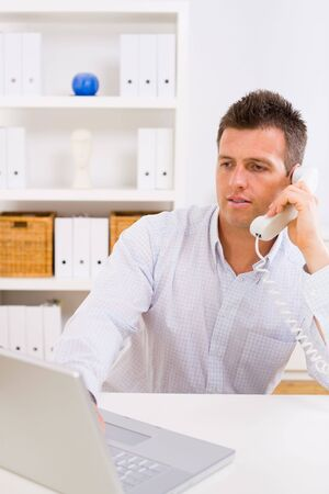 Business man working on computer at home calling on phone. Stock Photo - 3850867