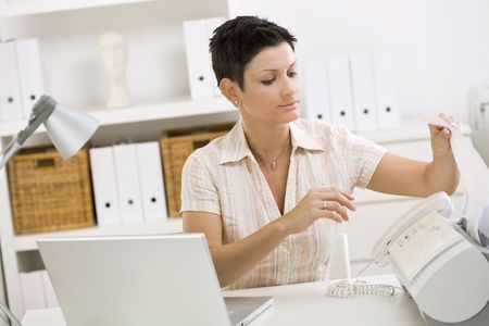 outworking: Woman using fax machine at home office. Stock Photo