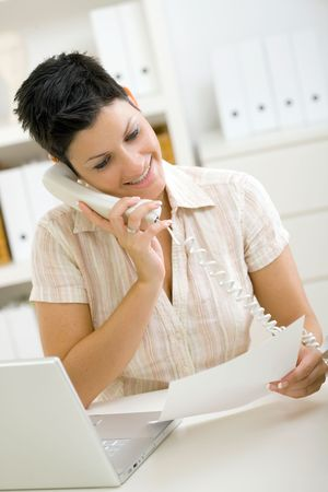 Happy woman calling on phone at home office. photo