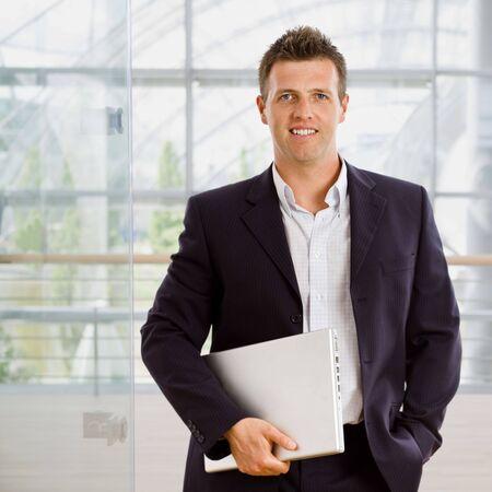 Happy businessman holding laptop computer indoor smiling. photo