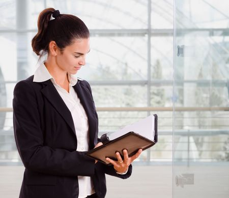 Attractive businesswoman looking at day planner in office lobby. Stock Photo - 3850842
