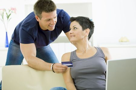 Happy couple paying with credit card at home, smiling. photo