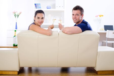 Love couple drinking champagne at home on sofa. photo