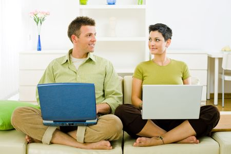 Happy couple working on laptop computer at home, smiling. Stock Photo - 3861566