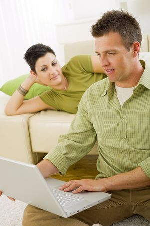 sinecure: Couple browsing internet on laptop on laptop computer at home. Stock Photo