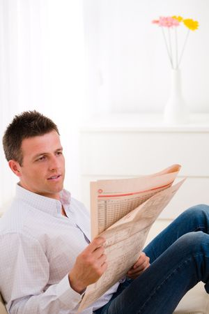 Man sitting on couch at home reading reading newspaper . photo