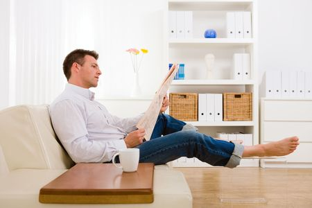 Man sitting on couch at home reading reading newspaper .
