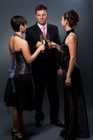 Three people drinking champagne on a party. photo
