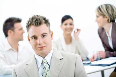 Portrait of young businessman with three colleagues sitting in background. photo