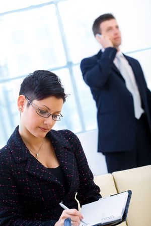 Young and attractive business people working in office. Businesswoman sitting on sofa writing to notebook while businessman calling on mobilephone. Stock Photo - 3868596