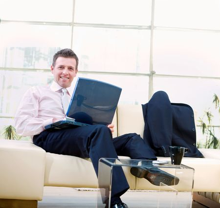 Happy businessman sitting on sofa at office, working on laptop computer and smiling. photo