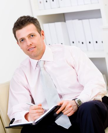 Happy businessman sitting on sofa at office and writing to notebook, smiling. photo