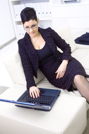 Young adult businesswoman sitting on sofa at office and working on laptop computer. photo