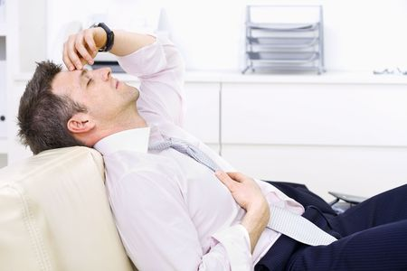 Mid-adult businessman lying on couch at office, looking exhausted eyes closed. Bright background. Stock Photo